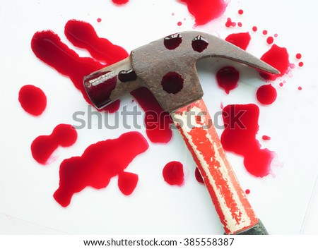 A close-up of a bloody hammer and small blood pool isolated on white. - stock photo