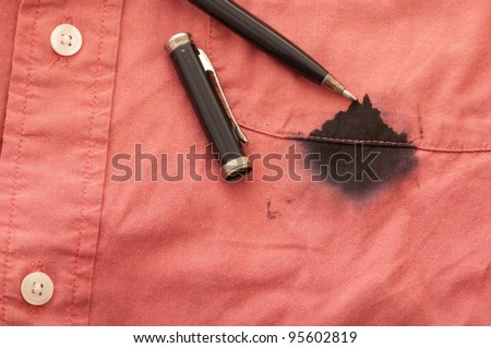 A Close Up of a Broken Pen Resting on the Men's Red Shirt Stained with Ink - stock photo