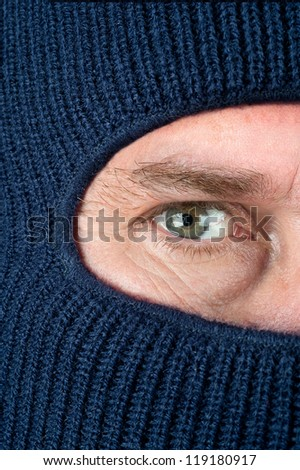 A close up of a burglar peering through a blue ski mask to hide his identity. - stock photo