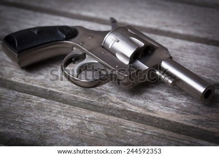 A close-up of a .32 caliber pistol on a gray wooden table, shallow depth of field. - stock photo