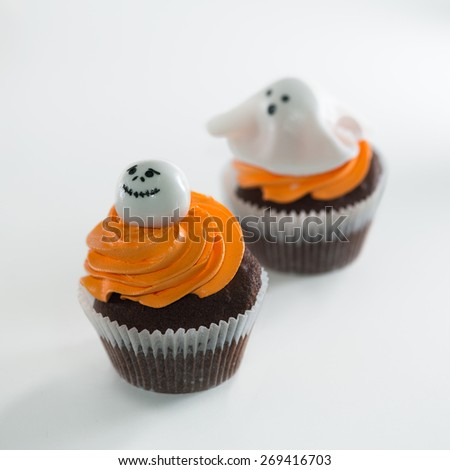 A close up of a chocolate cupcake, covered with Halloween decoration object on top, a little whipped cream and top with a fresh and luscious - stock photo