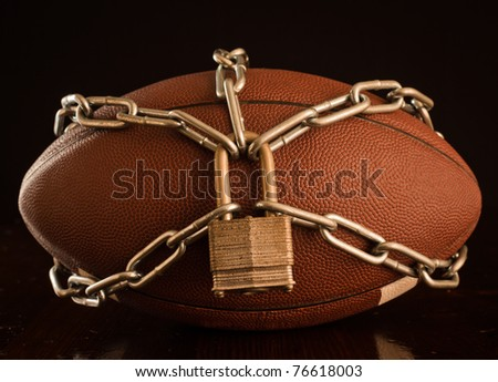 A close up of a football locked up with chain. - stock photo