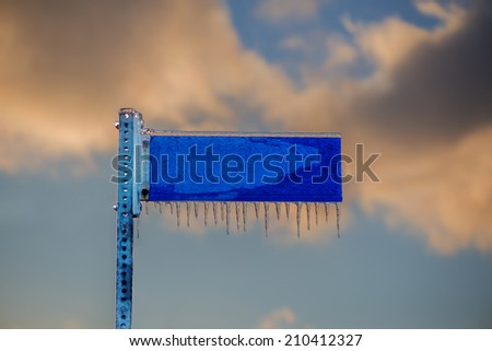 A close up of a frozen blank blue street sign covered in ice and icicles against a cloudy sky.  Room for copy space text.  - stock photo