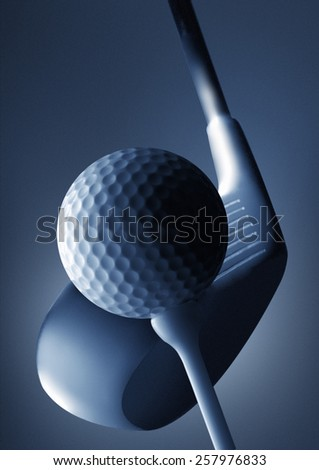 A close up of a golf club and golf ball on a tee - stock photo