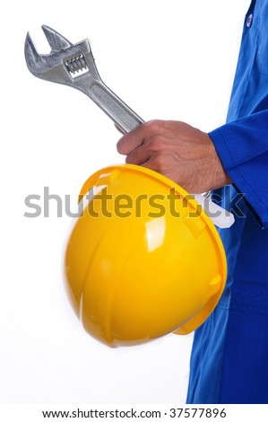 A close up of a man's left hand holding a yellow hardhat and wrench. The man is wearing a royal blue jumpsuit. - stock photo