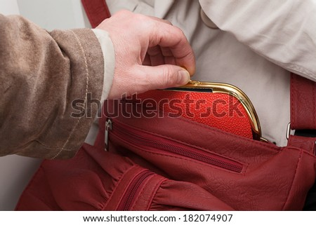 A close up of a man stealing a red purse - stock photo