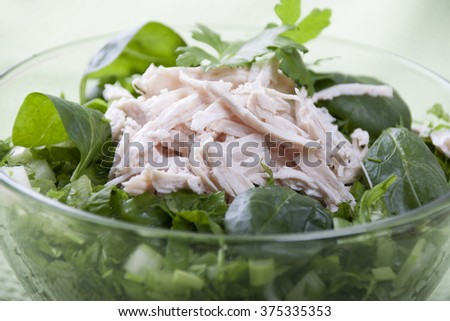 A close up of a mixed vegetable salad with chicken boiled meat. The salad is mostly green leafy lettuce. The salad is in a glass bowl. - stock photo