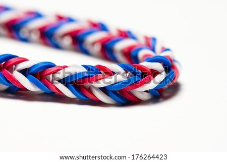 a close up of a red, white and blue rubber band bracelet - stock photo