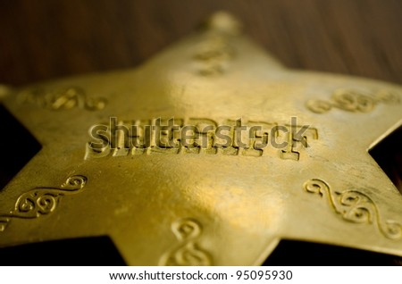 A close up of a sheriff's badge. Shallow depth of field used on purpose. - stock photo