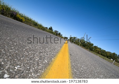 A close-up of a two lane road with a yellow line in the middle. - stock photo
