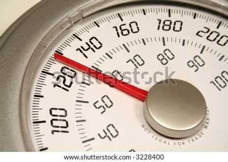 A close up of a weight scale set at 128. - stock photo