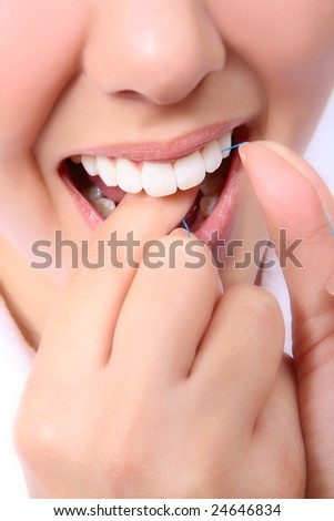 A close-up of a woman flossing her teeth - stock photo