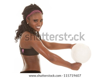 A close up of a woman getting ready to hit a volleyball with a smile on her face. - stock photo
