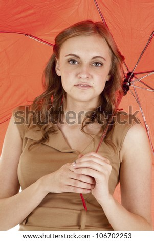A close up of a woman holding on to a red umbrella with a small smile on her lips. - stock photo