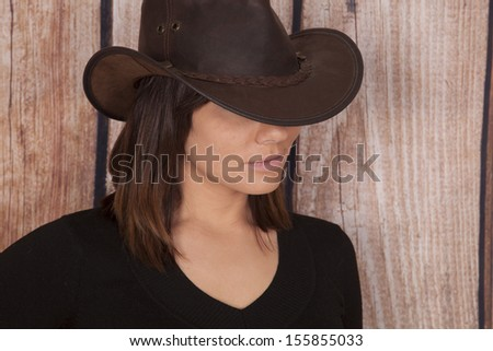 A close up of a woman in her cowgirl hat hiding her eyes. - stock photo
