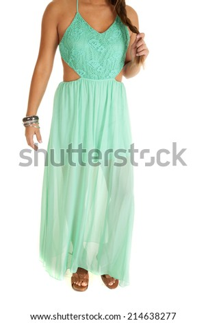 A close up of a woman in her teal dress, she is playing with her hair. - stock photo