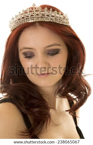 A close up of a woman looking down while wearing a crown on her head. - stock photo