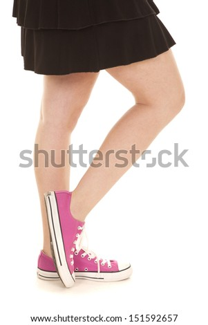 A close up of a woman's legs in her pink shoes - stock photo
