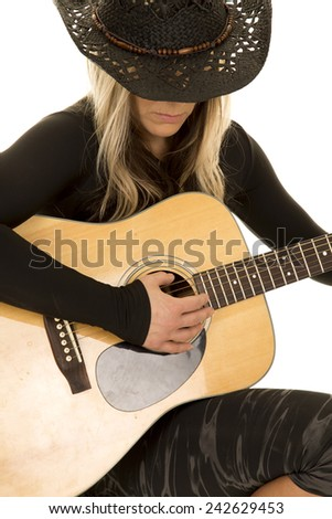 A close up of a woman with her cowgirl hat on looking down and playing her guitar. - stock photo