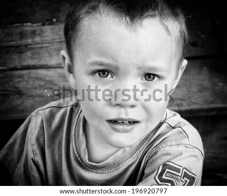A close up of a young boy with a serious look of concern.  Processed in black and white  - stock photo