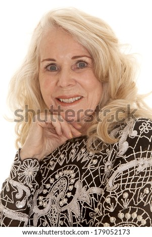 A close up of an elderly woman with her hand under her chin. - stock photo