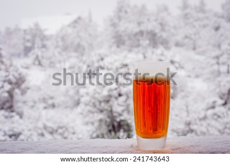 A close up of an ice cold beer sitting on a snow covered railing. - stock photo