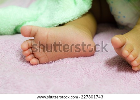 A close-up of baby feet. focused on foot. - stock photo