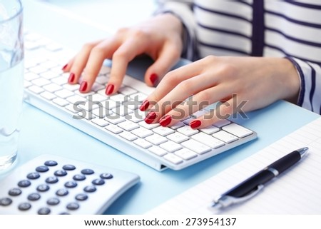 A close-up of businesswoman wearing a shirt seated at a desk with her fingers on a white computer keyboard. Business person working at office.  - stock photo