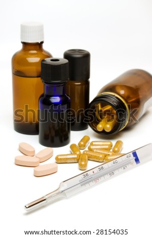 A close-up of essential oil bottles, capsules, pills and a thermometer. - stock photo