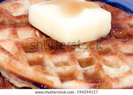 A close up of hot waffles with syrup and a big chunk of butter - stock photo