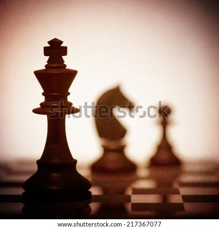 A close up of the King chess piece in silhouette with two other pieces in the background - stock photo