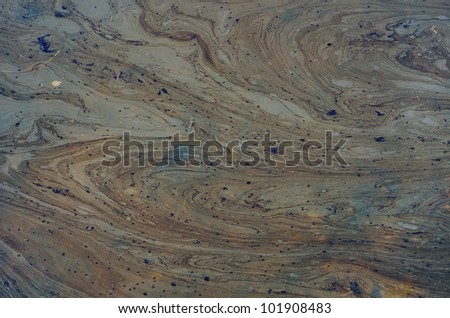 A close up of the surface of black oil pollution on water. - stock photo