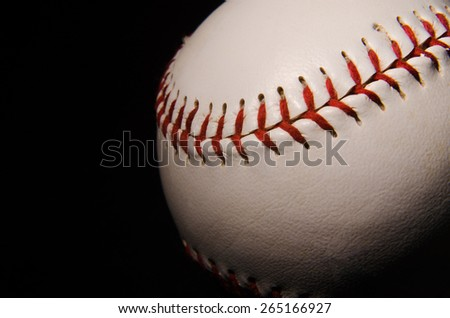 A close up of the threads of a single baseball on a black backdrop with single light illuminating it for isolation and drama. - stock photo