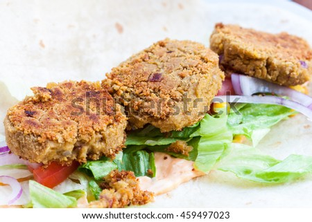 A close-up of three falafels sat on a salad on an open wrap - stock photo