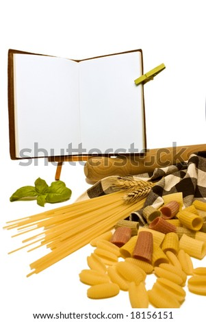 A close up of various pasta and an open blank recipe book. - stock photo