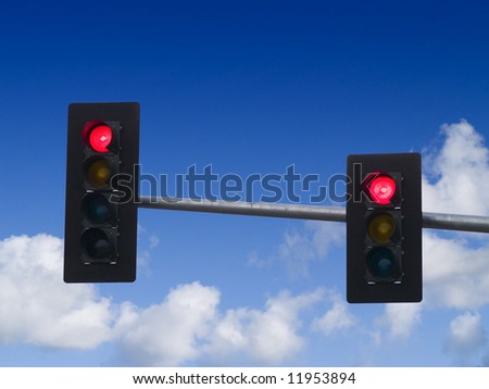 A close up on a red traffic light with blue sky and clouds in the background. - stock photo