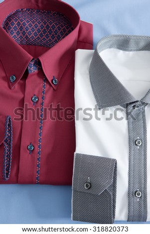 a close up on two folded tshirts on a blue background - stock photo