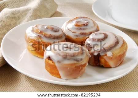 A close up photo of a plate of cinnamon rolls - stock photo