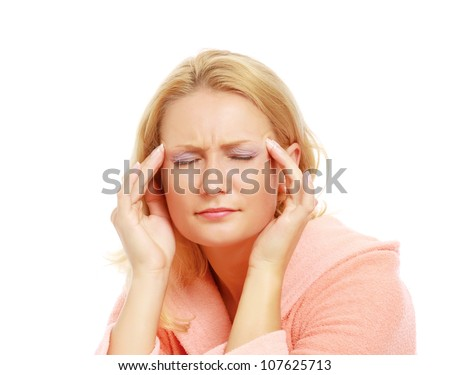 A close-up portrait of a woman with headache holding her hand to the head - stock photo