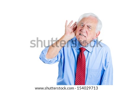 A close-up portrait of an elderly executive looking unhappy and annoyed,having trouble hearing his opponent, during unpleasant conversation, isolated on a white background . - stock photo