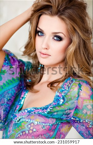A close-up portrait of sexy and slender young girl with blue in a blue dress - stock photo