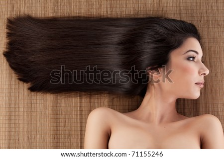 a close-up profile portrait of a young woman, laying on a spa mat. her hair is laying strait, in a horizontal direction. - stock photo