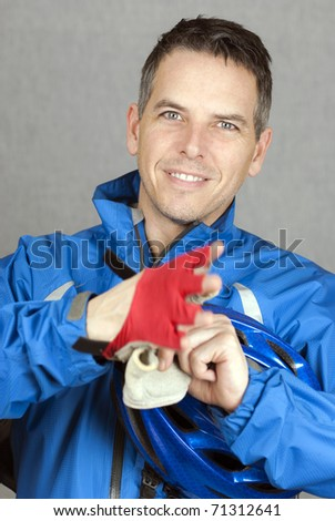 A close-up shot of a cyclist putting on his gloves. - stock photo