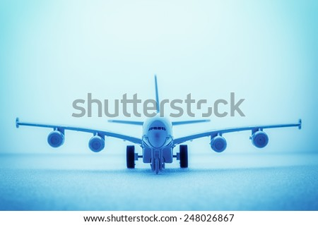 A close up shot of a die cast model plane selective DOF, abstract background, blue toning. - stock photo