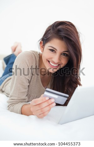 A close up shot of a smiling woman lying on the bed with a credit card and tablet in her hands. - stock photo