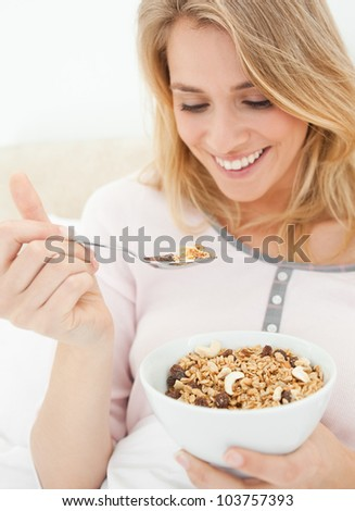 A close up shot of a woman holding a bowl of cereal and a raised spoon of cereal near to her mouth. - stock photo