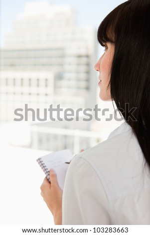 A close up shot of a woman with a notepad in hand as she stares upwards - stock photo