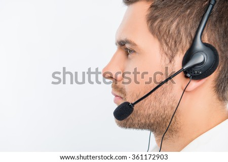 A close-up side-face portrait of a young agent of call centre - stock photo