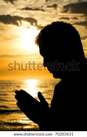 A close up silhouette of a man with his head bowed in prayer at the ocean. - stock photo