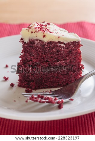 A close-up slice of red velvet cake with a piece missing on a white plate with a fork - stock photo